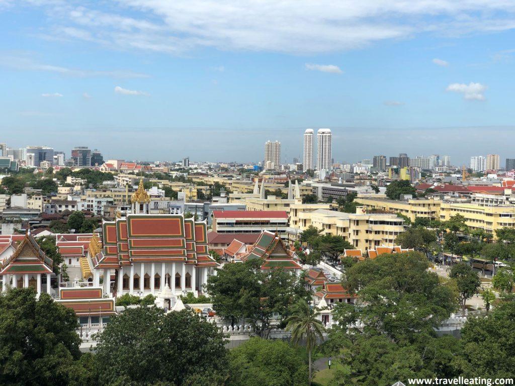 Vistas de la ciudad de Bangkok en la que destacan un gran templo y los edificios altos al fondo.