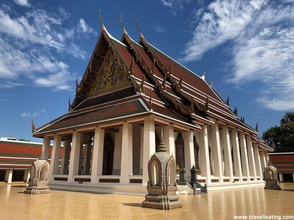 Edificio religioso blanco rodeado de columnas y con un tejado repleto de colores y detalles dorados.