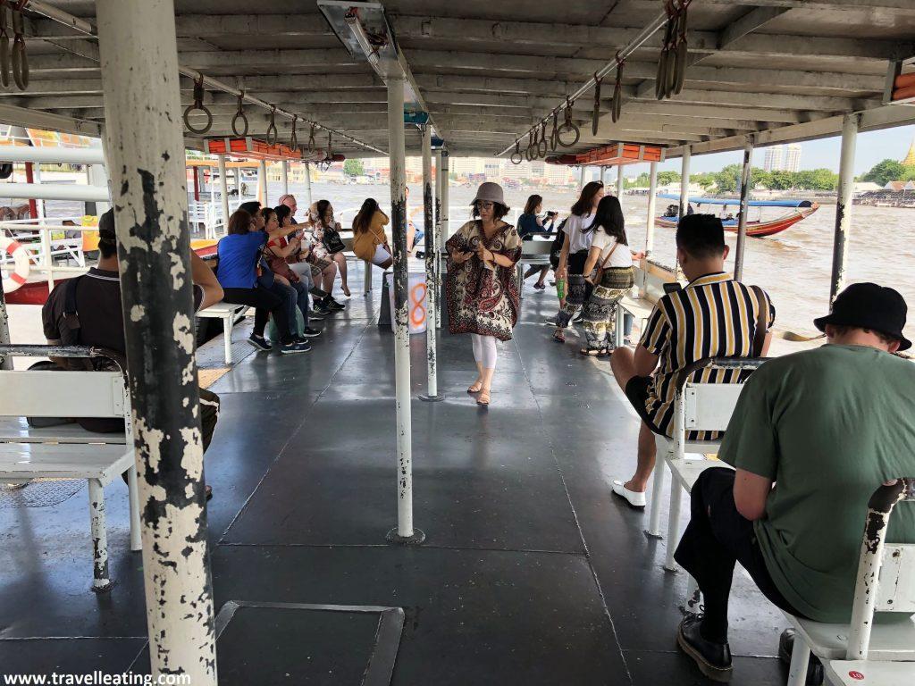 Barco amplio con bancos repleto de gente sentada, a excepción de una mujer que se encuentra de pie en el centro de éste.
