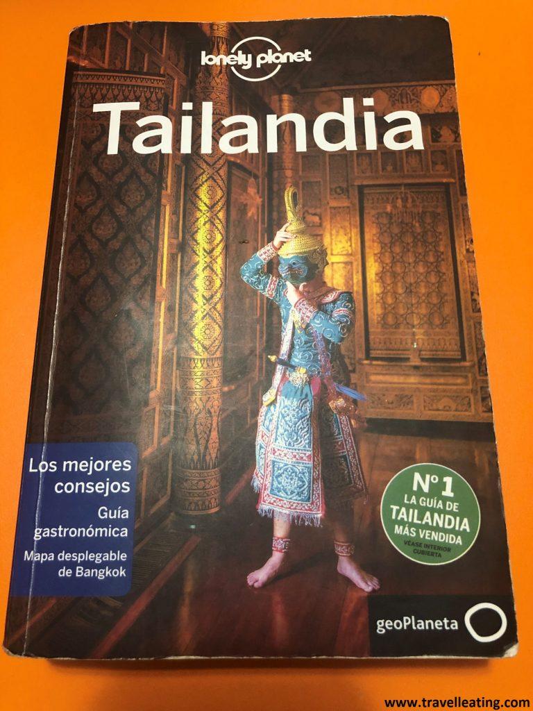 Guía de viajes de la marca Lonely Planet sobre Tailandia. En ella se ve un hombre vestido tradicionalmente.