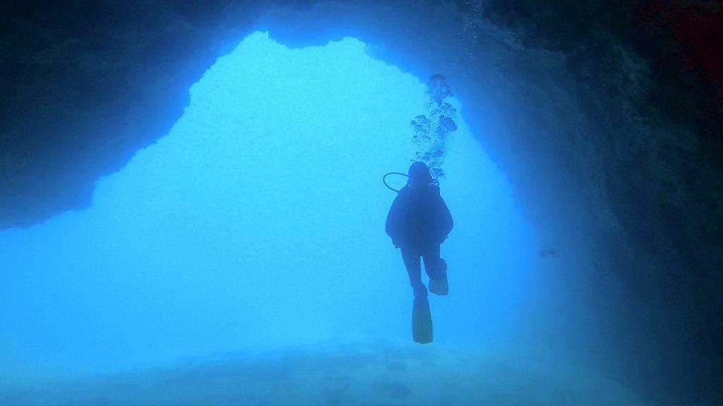 Gran cueva submarina en medio de la cual se ve un submarinista nadando. Se trata de la Catedral una de las mejores inmersiones que ver y hacer en Lanzarote.