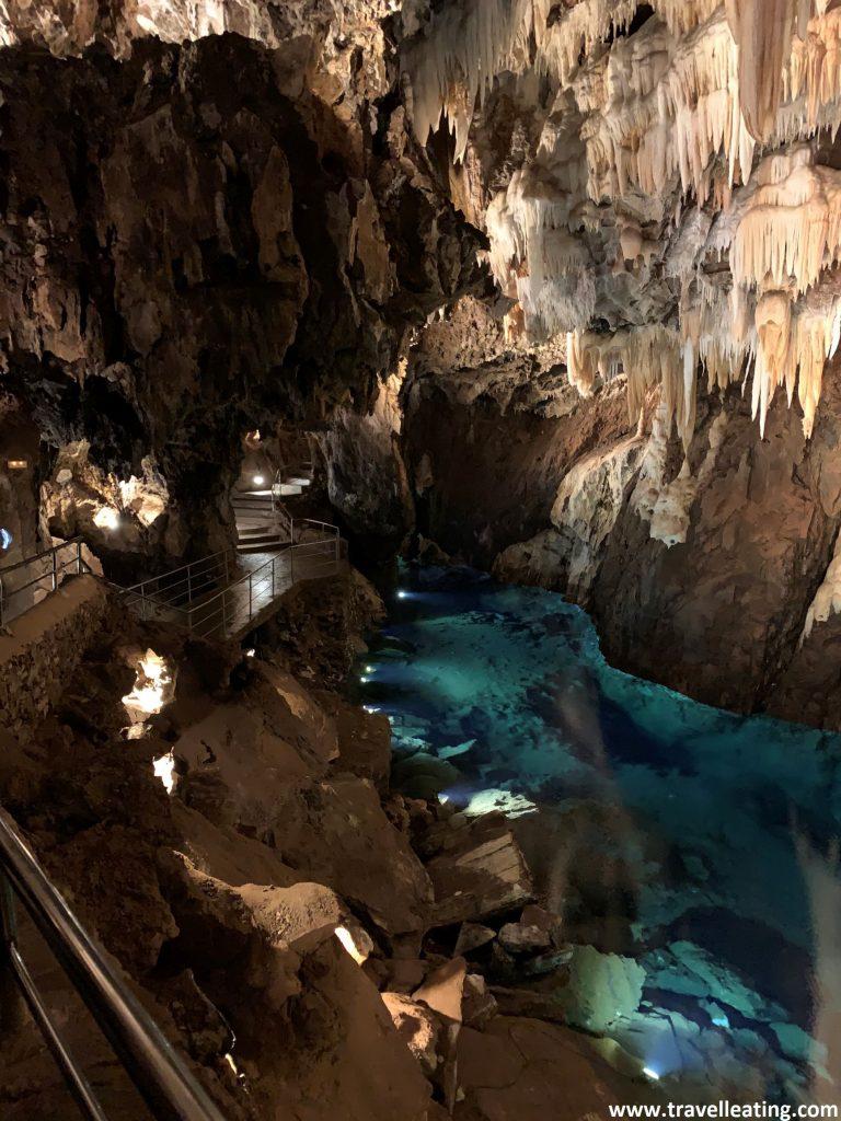 Interior de una cueva repleta de estalagmitas y estalactitas. También podemos ver un pequeño lago de un azul turquesa muy intenso.