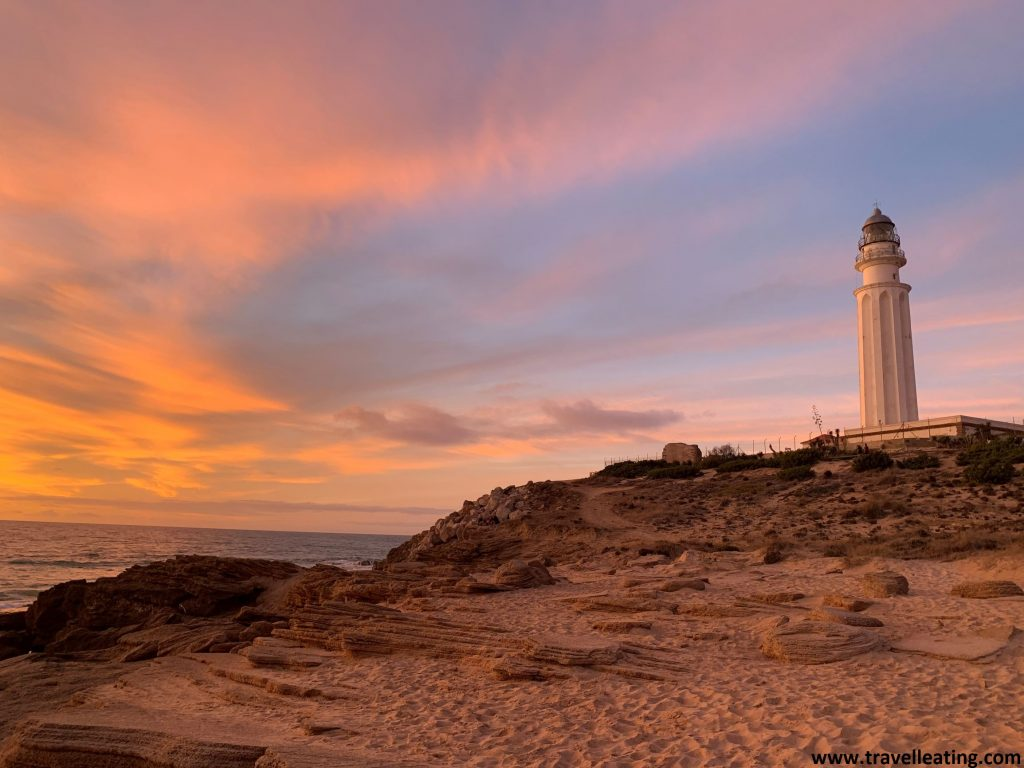 Precioso atardecer en frente de un faro blanco que se alza frente al mar. El cielo está teñido de colores rosas, naranjas y rojizos.