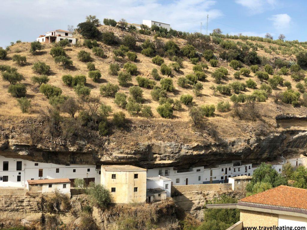 Curiosa calle contruida en la piedra, con sus casas incrustradas en ella, y sobre las cuales destacan unos campos.