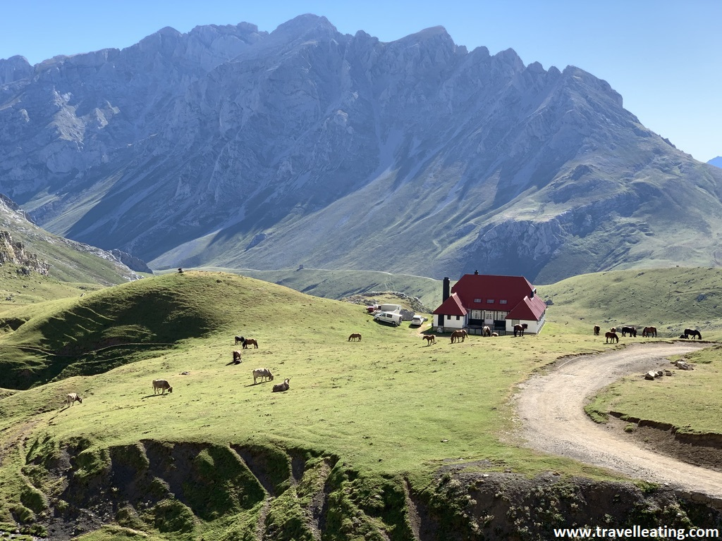 Paisaje de montaña en el que se ve una explanada con una pradera verde con caballos pastando, un refugio con el tejado rojo y tras éste, una preciosa montaña. Hacer una ruta por la montaña es una de las mejores cosas que hacer en Liébana.