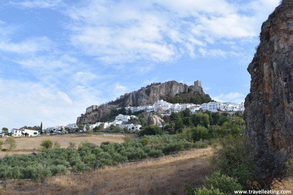 Vistas del precioso pueblo blanco de Zahara de la Sierra coronado por los restos de su antiguo castillo y rodeado de campos.
