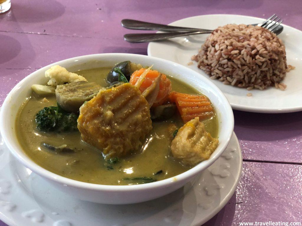 Bol de curry verde de verduras con tofu. Detrás de éste vemos un plato de arroz para acompañarlo. Otro plato típico de la gastronomía tailandesa.