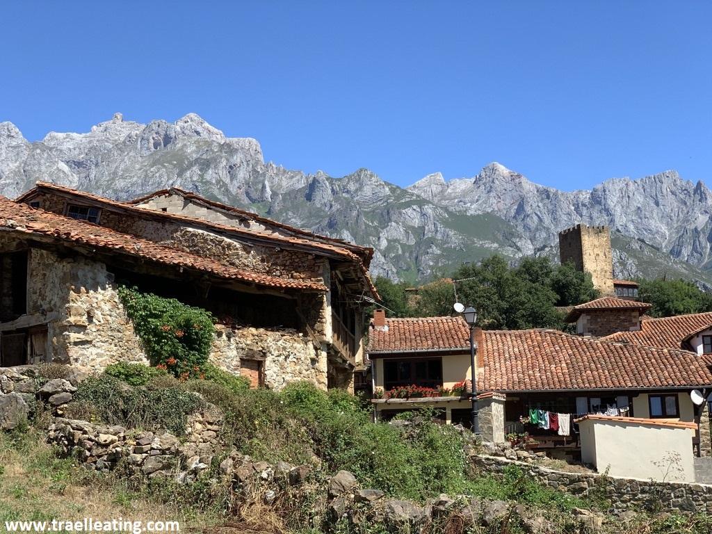 Vistas de un pueblo con casas de piedra de estilo tradicional entre las cuales sale una torre. Tras ellas se extienden las montañas. Este pueblo es una de las mejores cosas que ver y hacer en Liébana