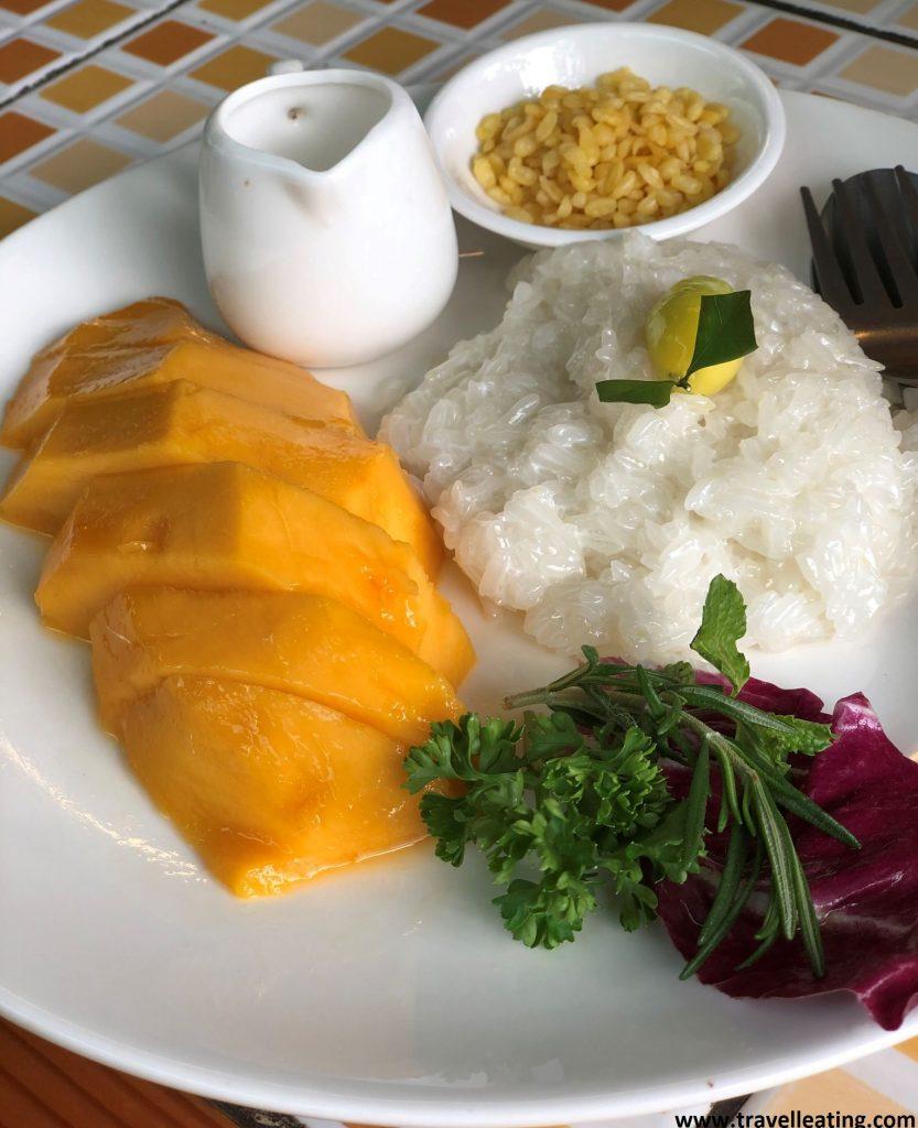 Plato con medio mango fresco cortado a rodajas servido con un montoncito de arroz glutinoso, un mini bol con arroz frito y un recipiente con leche de coco. El postre más bueno y popular de la gastronomía tailandesa.