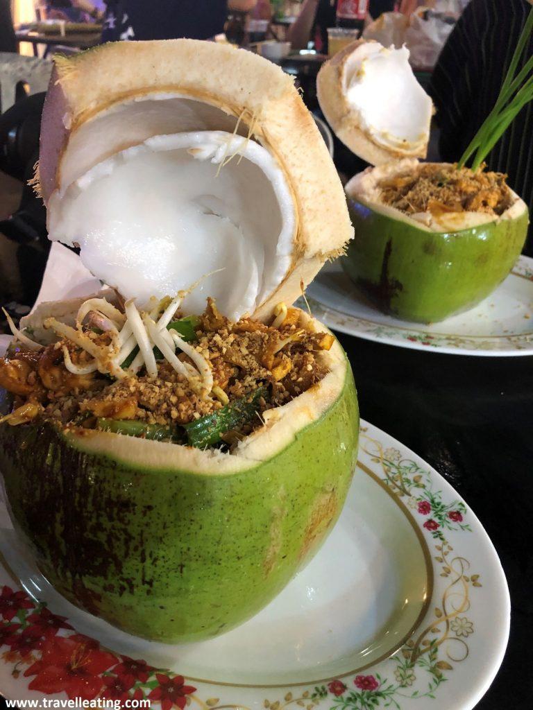 Dos cocos frescos abiertos y rellenados con Pad Thai, estos fideos típicos de la gastronomía tailandesa.