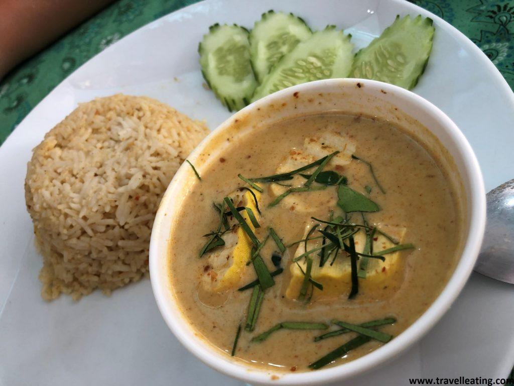 Bol de panang curry, una sopa de curry hecha a base de cacauetes, con tofu y hierbas por encima, acompañado de un montoncito de arroz y pepino troceado.