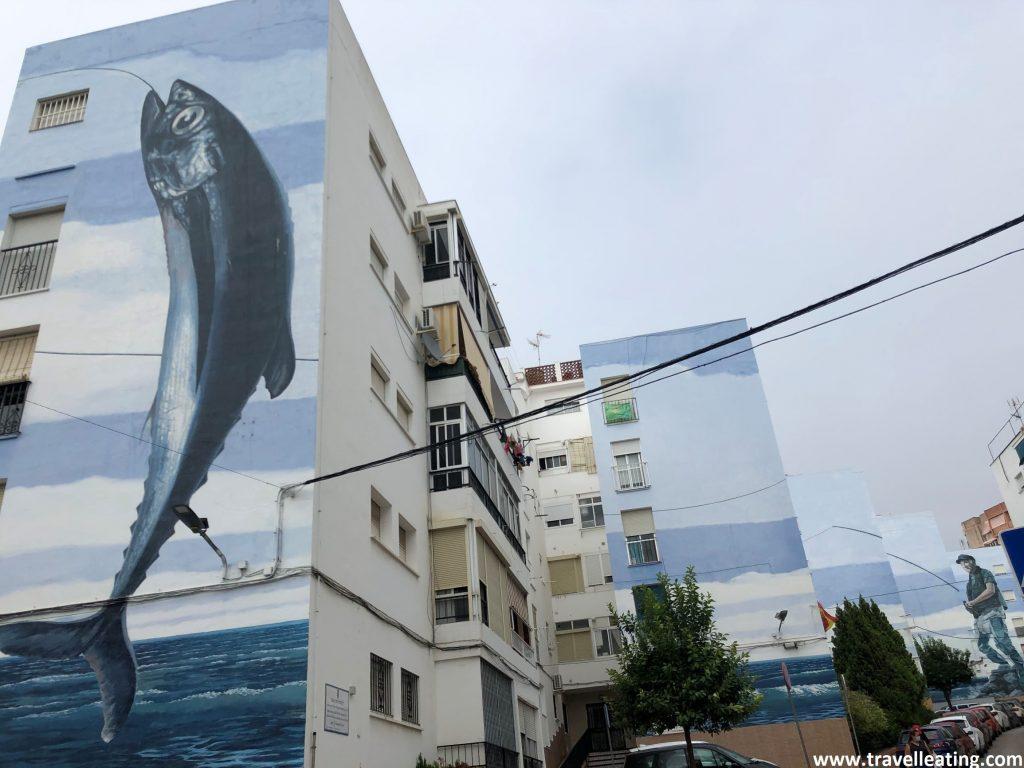 Mural que ocupa seis fachadas consecutivas. En la primera se observa un pez enorme cogido por un anzuelo y en la última un pescador con una caña.
