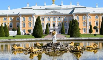 En la foto vemos la fachada principal del Palacio Peterhof, de color amarillo pastel y azul muy claro. Delante de él luce un camino franqueado por setos y delante de éste, una hermosa fuente con esculturas en medio.