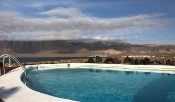 Piscina turquesa al aire libre con vistas a un impresionante risco que se alza sobre el mar.